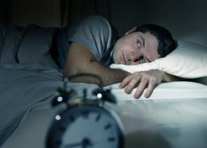 A man laying awaking in bed.