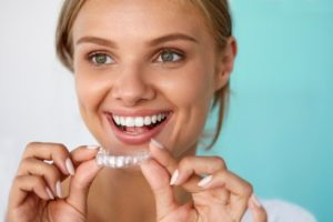 Woman holding clear aligner from a dentist in Uptown Houston.